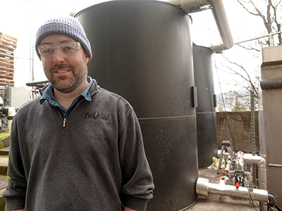 Full Sail Brewery's Quality Assurance Manager Kevin McCabe, Ph.D., in front of the brewery's two pretreatment tanks.